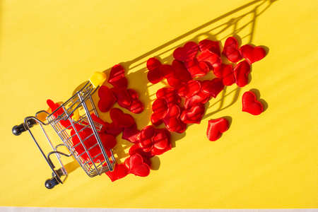 shopping trolley overturned, and red hearts fell out of it, a yellow background. Buy love concept, flatlay.
