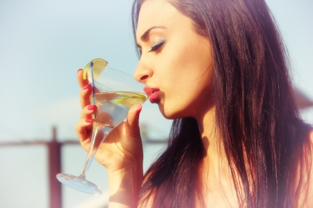 Attractive young girl drinking martini photo
