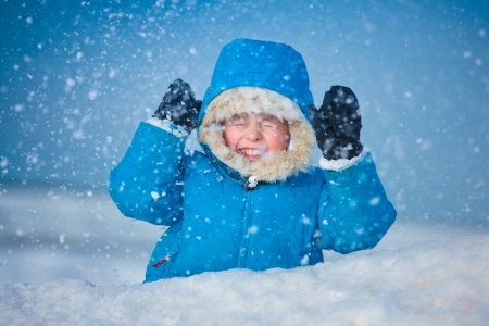 Portrait of a little boy playing outdoors in the snow photo