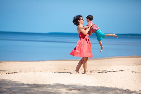 Mother and her little son playing on the beach Stock Photo