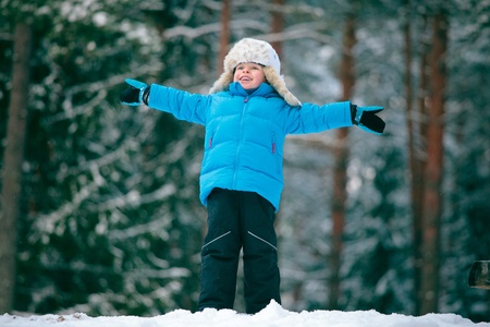 Portrait of a little boy playing outdoors in a winter forest