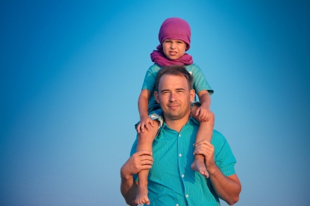 Little boy sitting on father s shoulders photo