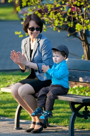 Young mother and her son sitting on bench Stock Photo