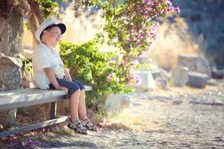 Three years old boy sitting on bench photo