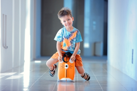 Cute three years old boy sitting on a suitcase photo