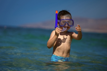 A boy in a sea with a swimming mask and snorkel photo