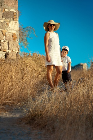Mother and her cute little son walking outdoors photo