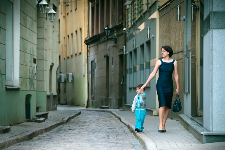 Mother and her little son walking in city photo