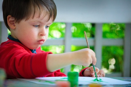 Three years old boy painting with brush