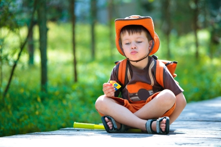 niño con mochila: Boy tener resto en bosque de verano Foto de archivo