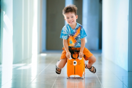 Boy laughs and sitting on a suitcase at airport