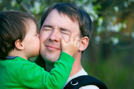 Little son kissing his father outdoors Stock Photo - 13689060