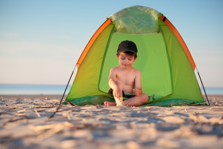 Little boy playing in his tent on the beach  photo