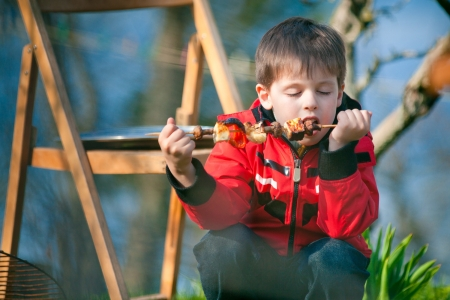 Little boy with pleasure eats grilled vegetables photo