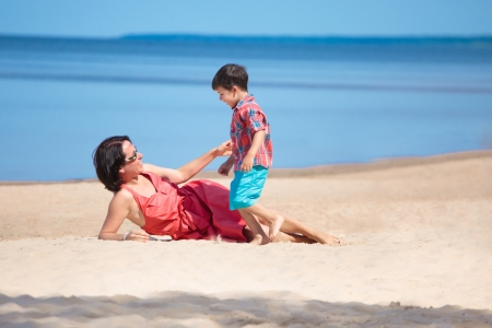 Mother and her little son playing on the beach  photo