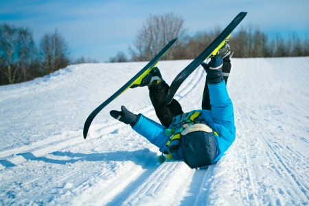 Boy with cross-country skis lying on snow  photo