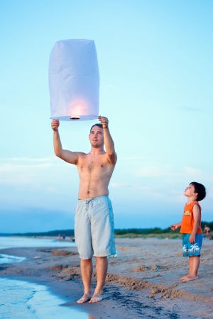 Happy dad and son flying fire lantern together