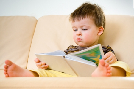 innocence: Little boy reading book on sofa