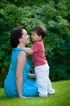 Two years old boy hugs his young mom in park