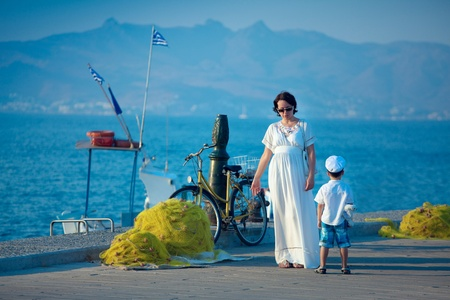 maxi dress: Young woman on maxi white dress and her little son talking on jetty by the sea Stock Photo