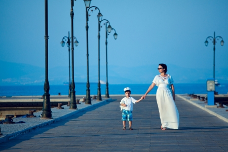 Happy beautiful woman on maxi white dress and her little son on wooden jetty by the sea