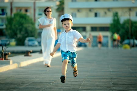 Little boy and his mother running at jetty in summer day
