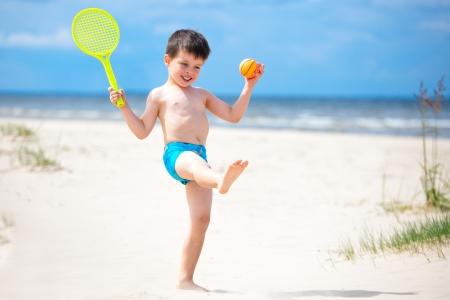 Niño feliz jugando con la pelota y la raqueta de tenis en la playa tropical