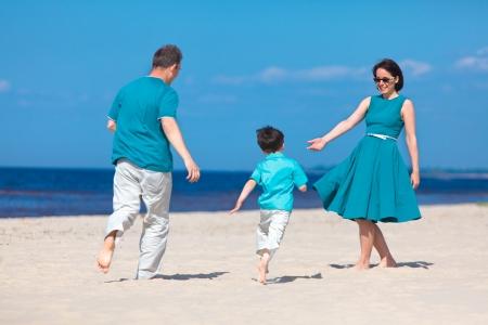 Young beautiful family of three having fun tropical beach  photo