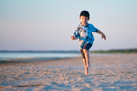 Boy running on sand beach on summer day Фото со стока