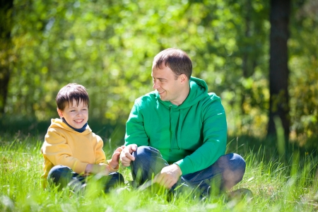 Young father with his son in summer day in the park photo