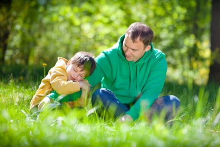 Cute little boy hugs his father in summer day in the park Stock Photo