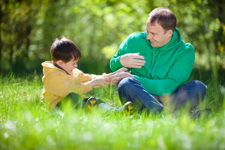 Happy father playing with his little son in the park in summer day