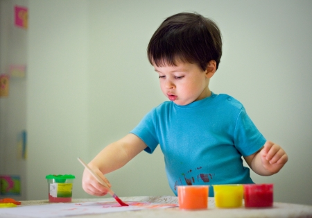 Cute toddler boy painting with brush at home