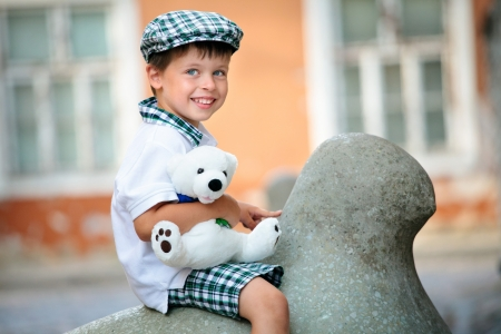 Close up portrait of happy little boy outdoors in city on beautiful spring day  Stock Photo