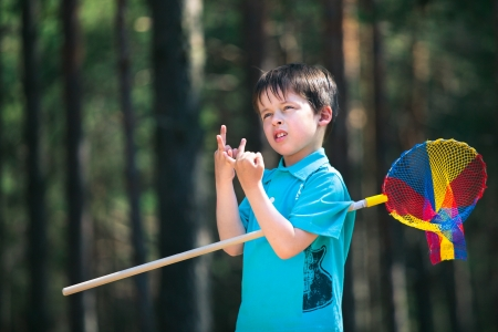 Cute little boy counting with his fingers during his walking at forest
