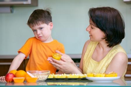 dislike: Schattige kleine jongen weigert te proeven zelfgemaakte muffin, is kind niet wil eten Stockfoto