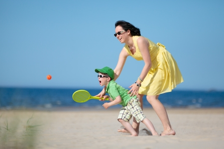 Young loving mother and her four years old son playing on the beach