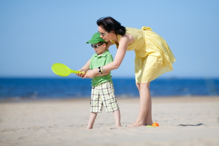 Young mother teaching her son to play tennis on the beach photo