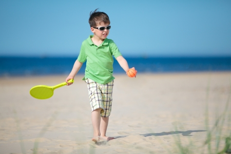 Cute little boy playing with tennis racket on tropical beach photo