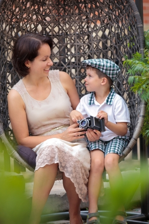Mother and son sitting on the cane-chair and holding retro camera