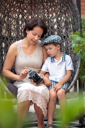 Mother and son sitting on the cane-chair and holding retro camera photo