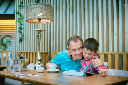 Father and his little son relaxing  and looking at laptop screen in cafe