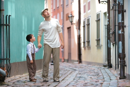 Father and son walking outdoors in city on beautiful summer day