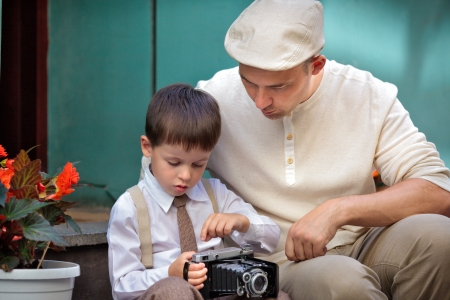 Young father and son outdoors with retro camera on their hands Stock Photo