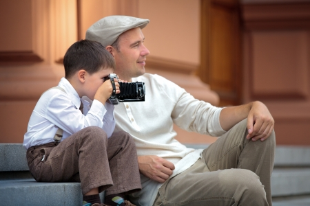 Father and little son holding retro camera in city on beautiful summer day  Фото со стока