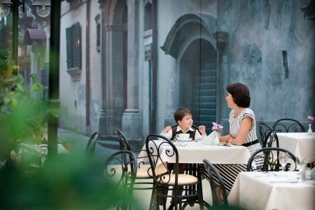 madre hijo: Madre e hijo que se sienta en el caf� en el centro comercial