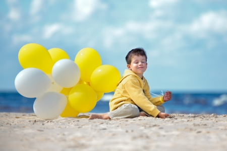 Cute little boy with yellow balloons on the beach on beautiful summer day photo