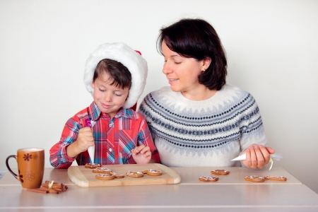 Young mother and her little son decorating the gingerbread cookies photo