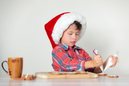 Cute little boy decorating the gingerbread cookies, Merry Christmas photo