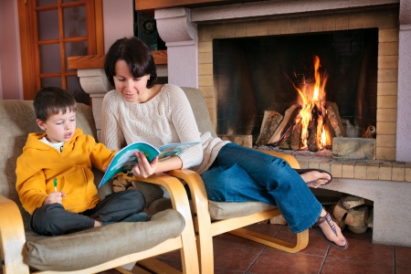 fireplace home: Mother and son reading a book in front of fireplace  Story Time